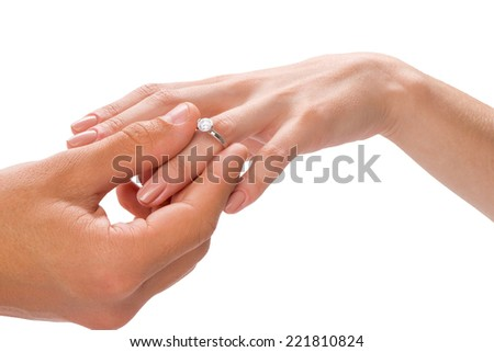 Close-up of the groom and bride exchanging rings, isolated on white - stock photo