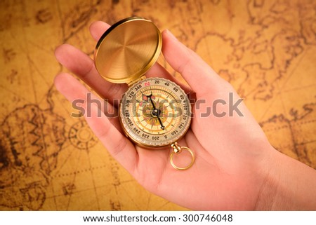 Close up of the hand holding a vintage compass over a vintage map - stock photo