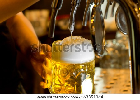 Close up of the hand of a man pouring a tankard of frothy draught beer from a stainless steel beer tap in a bar or pub into a large glass tankard - stock photo