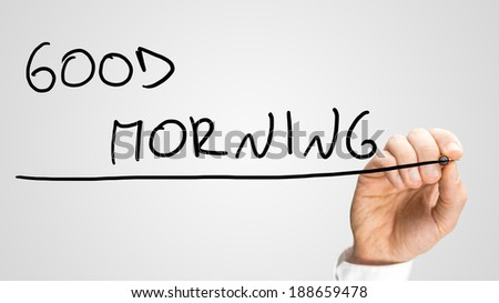 Close up of the hand of a man writing Good morning on a virtual screen or interface with a marker pen with copyspace below. - stock photo