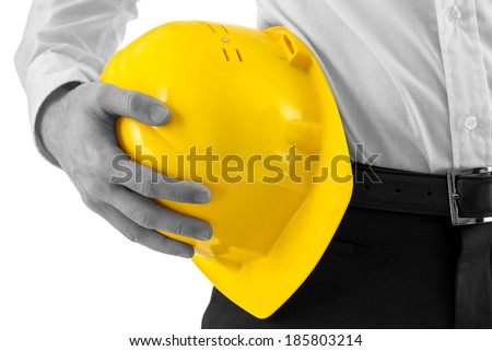 Close up of the hand of a professional man carrying a yellow hard hat against his hip with selective color conceptual of an architect, engineer, building and construction. - stock photo