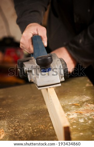 Close up of the hand of an elderly man planing a plank of wood in his carpentry workshop with a plane to smooth the surface - stock photo
