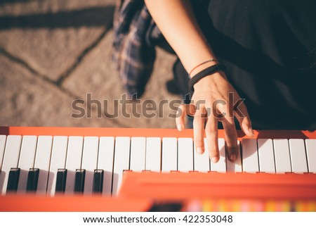 Close up of the hand of young woman playing piano - creative, performance, music concept - she is dressed with a black shirt and plays a red piano - stock photo