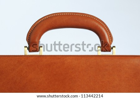 close up of the handle on a leather business briefcase - stock photo