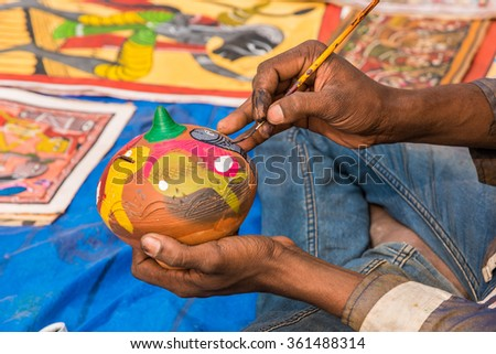 Close up of the hands of a artist painting colorful earthen pot piggy bank. - stock photo