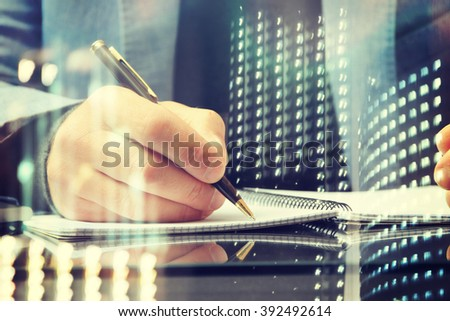 Close up of the hands of a businessman in a suit signing or writing a document  - stock photo
