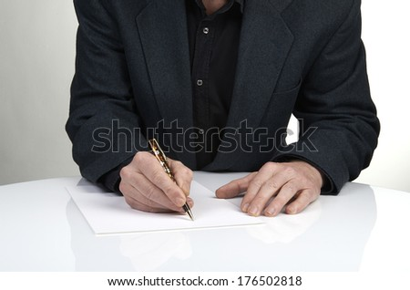 Close up of the hands of a businessman in a suit signing or writing a document on a sheet of white paper using a fountain pen