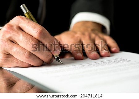 Close up of the hands of a businessman signing a typed document with a fountain pen with copyspace in the foreground. - stock photo