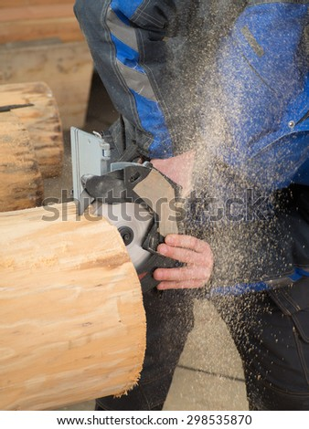 Close up of the hands of a carpenter holding a hand circular saw and cutting a tree trunk
