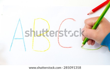 Close up of the hands of a little child writing letters with color pencils