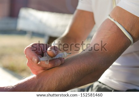 Close-up of the hands of a man injecting a drug dose intravenously - stock photo