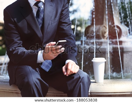 Close up of the hands of the businessman with a mobile phone and coffee near the fountain. Outdoors - stock photo
