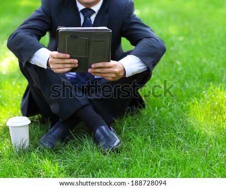 Close up of the hands of the businessman with a tablet PC. Outdoors - stock photo