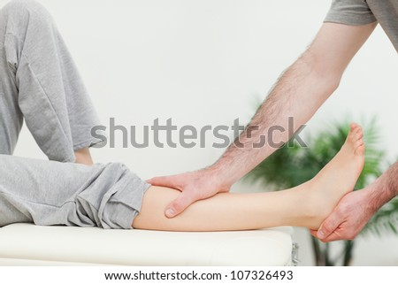 Close-up of the leg of a woman being stretched in a room