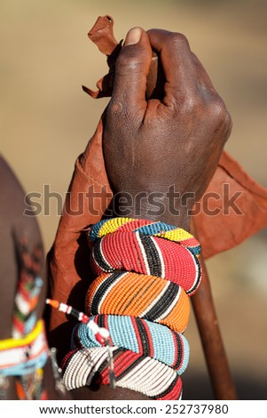 Close-up of the lower arm of a Samburu warrior in Kenya with colorful traditional bracelets and wristbands - stock photo
