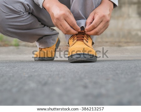 Close up of The man siting to wears safety shoes on street