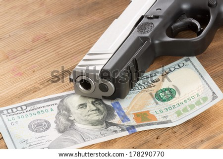 Close up of the muzzle of a gun with a 100 American dollar bill lying on a wooden table in a conceptual image of crime, bribery and corruption - stock photo