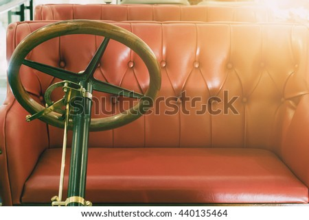 Close up of the old steering car and red leather seat. Image made vintage tone. - stock photo