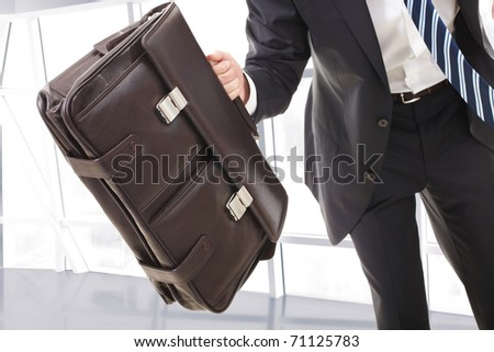 Close-up of the portfolio held by running man - stock photo