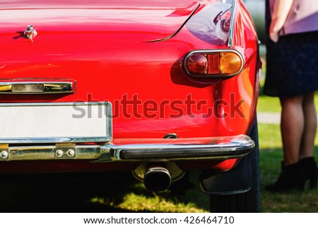 Close-up of the rear of the red vintage car. Back view of retro car. Vintage red car. Detail of a vintage car. Shallow depth of field. Selective focus. - stock photo