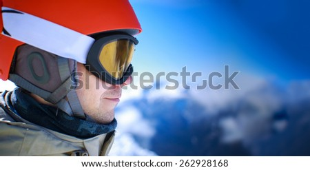Close up of the ski goggles of a man with the mountains at background - stock photo