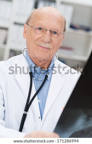Close-up of the smiling face of a balding senior doctor wearing glasses checking an x-ray film for a prognosis or diagnosis - stock photo