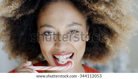 Close up of the smiling face of an attractive young woman biting a festive candy cane  symbolic of Christmas and the holiday season