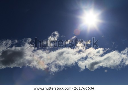 close-up of the solar disk and cloud against a blue sky on a sunny day - stock photo