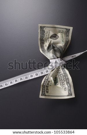 close up of the us currency and tape measure - stock photo