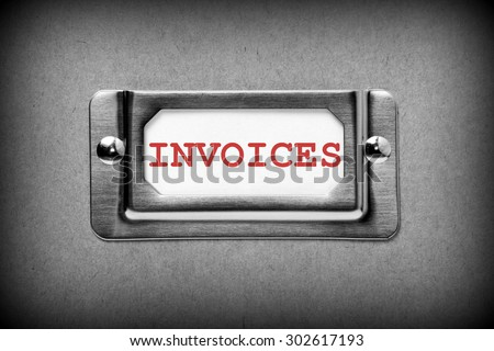 Close up of the word Invoices in red text on a drawer label holder from a filing cabinet. Processed in black and white for effect