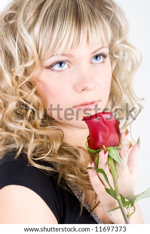 Close-up of the young blond girl face with a rose - stock photo