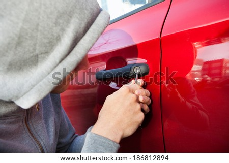 Close-up of thief in hooded jacket opening car's door - stock photo