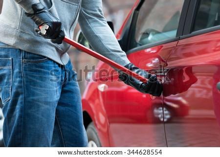 Close-up Of Thief Opening Car's Door With Crowbar - stock photo