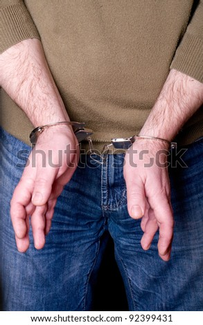 close up of thief's hands in handcuffs
