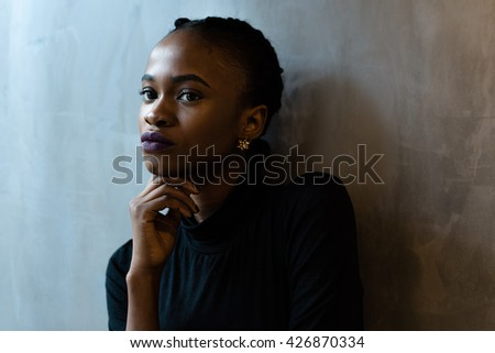 Close-up of thoughtful young black woman looking away with hand under the chin, gray background - stock photo