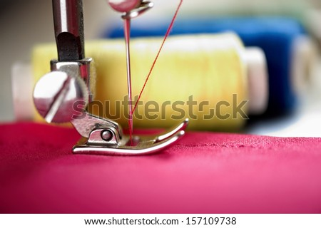 Close up of threads on fabric and sewing machine. Shalow DOF. Selective focus. Focus on blue threads. - stock photo