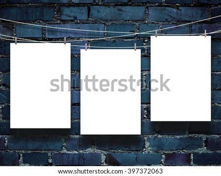 Close-up of three blank frames with pegs against blue brick wall background