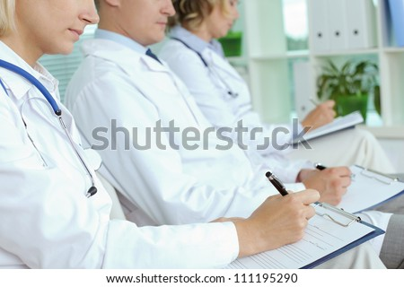 Close-up of three clinicians with clipboards making notes at medical conference - stock photo