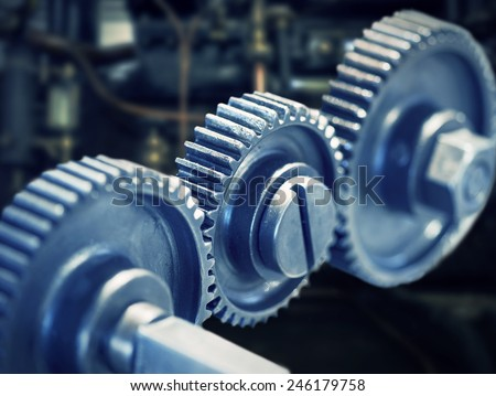 Close up of three cog wheels with machinery in background - stock photo