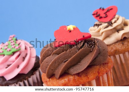 Close up of three cupcakes on a blue background - stock photo