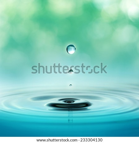 close up of three droplets in a blurred green background - stock photo