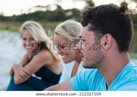 Close up of three friends laughing and talking on the beach - stock photo