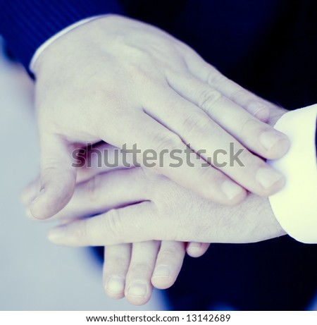 close up of three hands of businesspeople on top of each other - stock photo