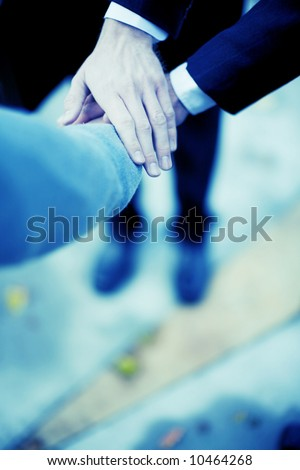 close-up of three hands on top of each other - stock photo
