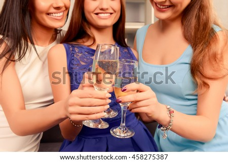 Close up of three happy smiling women holding glasses with shampagne