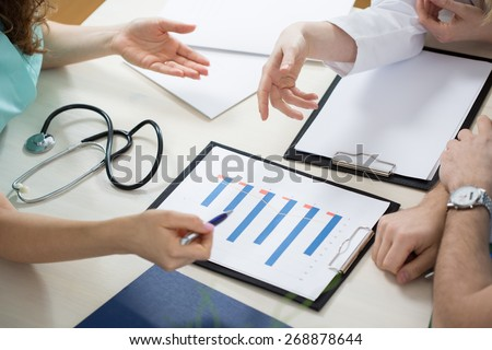 Close-up of three physicians looking at test results - stock photo