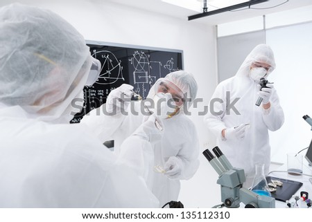close-up of three researchers analysing and evaluating chemical reactions in a chemistry lab using lab tools and a blackboard on the background - stock photo