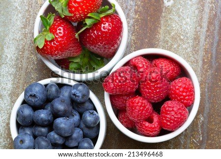 Close up of three small bowls overflowing with summer berries like strawberries, raspberries, blueberries - stock photo