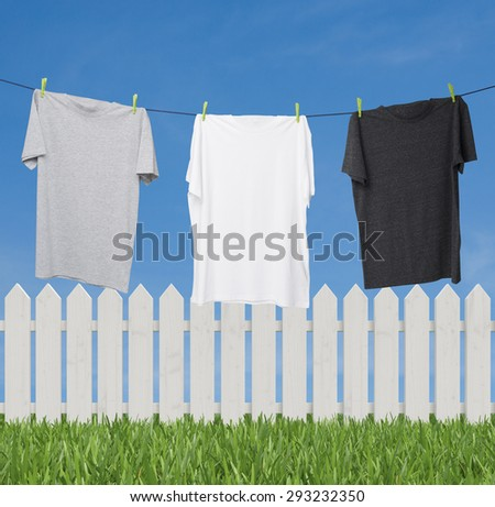 Close up of three t-shirts on the rope (grey, white and dark grey). Outside background with sky and green grass. - stock photo