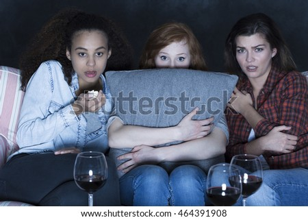 Close-up of three teenagers in a dark room, with frightened impressions on their faces while watching a movie